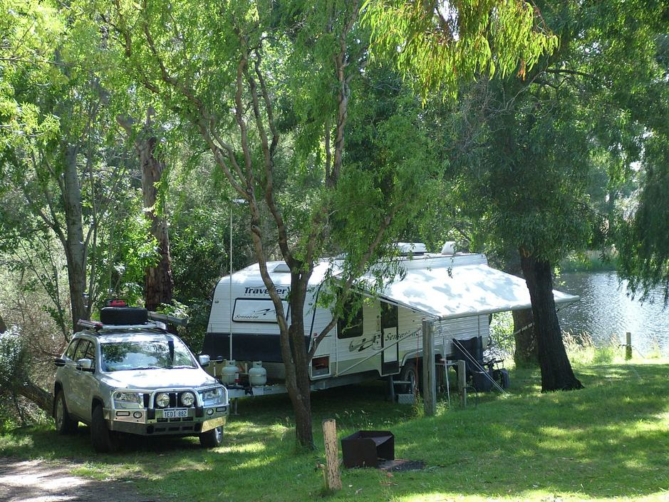 Green, grassy and shady caravan and camping sites with powered beside the lake at Grampians Paradise Camping and Caravan Parkland