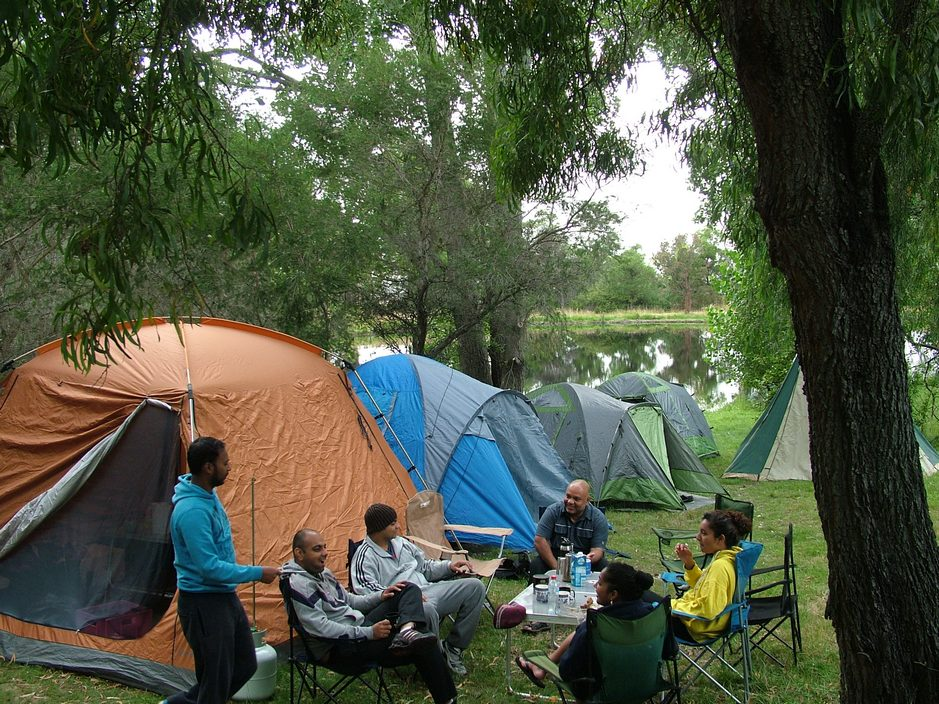 A group of friends enjoy camping on the large green grassy sites at Grampians Paradise Camping and Carvan Parkland